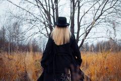 Porträt der jungen attraktiven Frau im schwarzen Mantel und im Hut Sie läuft das Feld durch Herbstlandschaft, trockenes Gras blic Stockfotografie
