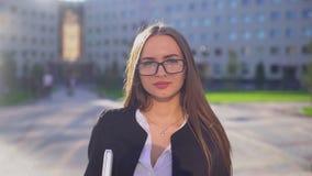 Porträt der jungen attraktiven kaukasischen Geschäftsfrau oder der Studentin mit Gläsern und Anzug Frauenholding stock video
