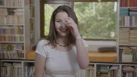 Porträt der jungen attraktiven Studentenfrau, die im Bibliothekscampus lächelt - stock video