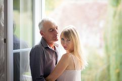 Porträt der jungen Blond-haarigen Frau im kurzen Sommer-Kleid, das nahe dem Fenster mit ihrem älteren Ehemann steht paare Stockbilder