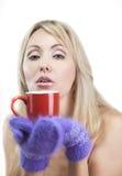 Porträt der jungen Blondine in den flaumigen Handschuhen mit einem Becher Lizenzfreie Stockfotos