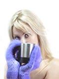 Porträt der jungen Blondine in den flaumigen Handschuhen mit einem Becher Stockfotos