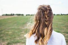 Porträt der jungen Blondine von hinten mit dem unvorsichtig geflochtenen Zopf- und Fliegenhaar im Wind auf dem Gebiet lizenzfreies stockfoto