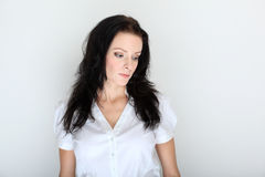 Porträt der jungen Brunettefrau in einem Gesellschaftskleidungcode mit geradem Gesicht Lizenzfreie Stockfotografie