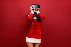 Porträt der jungen Brunettefrau im roten Samtkleid unter Verwendung des Kopfhörers der virtuellen Realität und des rührenden Kopf Lizenzfreie Stockfotos