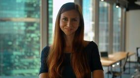 Porträt der jungen erfolgreichen Damenunternehmerstellung im Büroflur Drehengesicht zur Kamera stock video footage