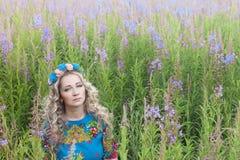 Porträt der jungen ernsten Frau unter den Blumen Stockfotografie