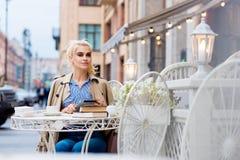 Porträt der jungen erstaunlichen Frau, die digitale Tablette verwendet, beim Sitzen im Straßencafé während ihrer Erholungszeit, Stockbilder