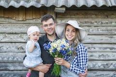Porträt der jungen Familie mit der Babytochter, die zusammen vor altem Retro- Holzhaus steht Stockfoto