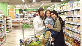 Porträt der jungen Familie mit Tochter im Supermarkt, kaufen sie Saft für Kind stock video