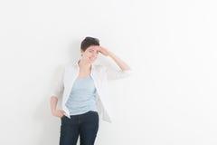 Porträt der jungen Frau über hellgrauem Hintergrund Frau, die Vorwärts- und schaut, setzend ihre Palme zur Stirn Stockbild