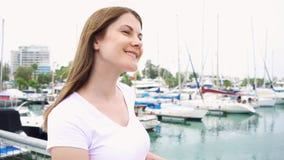 Porträt der jungen Frau allein stehend auf Pier Wind vom Meer, das weibliches Haar in der Zeitlupe durchbrennt stock footage