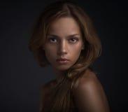 Porträt der jungen Frau auf dunklem backround Stockbilder
