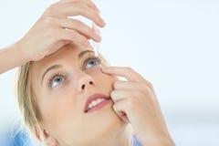 Porträt der jungen Frau Augentropfen setzend Stockfotos