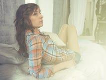 Porträt der jungen Frau in Bett gekleidetem zufälligem Hemd, Sun-Licht, getonte, warme Farben Stockfotografie