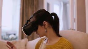 Porträt der jungen Frau in den Gläsern der virtuellen Realität, die zu Hause auf dem Sofa sitzen Weibliches herum schauen im VR-K stock video footage