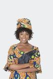 Porträt der jungen Frau in den stehenden Armen der afrikanischen Druckkleidung kreuzte über grauem Hintergrund Stockbilder