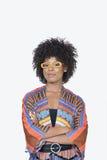 Porträt der jungen Frau in den stehenden Händen der afrikanischen Druckkleidung faltete grauen Hintergrund zusammen Stockfotografie