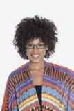 Porträt der jungen Frau in der afrikanischen Druckkleidung, die über grauem Hintergrund steht Stockbilder