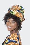 Porträt der jungen Frau in der afrikanischen Druckkleidung, die über Schulter gegen grauen Hintergrund schaut Lizenzfreie Stockfotos