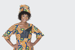 Porträt der jungen Frau in der afrikanischen Druckkleidung, die mit den Händen auf Hüften über grauem Hintergrund steht Lizenzfreies Stockbild