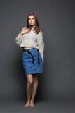Porträt der jungen Frau der Schönheit im weiblichen Pullover der weißen Mode und im Blue Jeans-Rock auf grauem Hintergrund Stockfotos