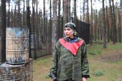 Porträt der jungen Frau in der Tarnung mit einem Gewehr draußen stockfotografie