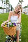 Porträt der jungen Frau des hübschen Gesichtes, die im Park mit ihrem klassischen Fahrrad und in den Blicken an der Kamera steht Lizenzfreie Stockfotos