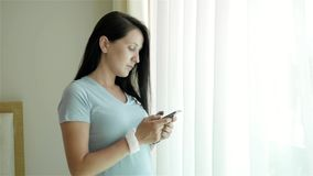 Porträt der jungen Frau, die Smartphone verwendet Kaukasisches vorbildliches Standing am Fenster und verwenden ihr Smartphone stock footage