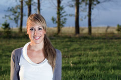 Porträt der jungen Frau draußen lächelnd Stockbild