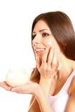 Porträt der jungen Frau Feuchtigkeitscremecreme auf ihrem hübschen auftragend lizenzfreies stockbild