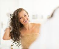 Porträt der jungen Frau Haar mit Tuch abwischend stockfotografie