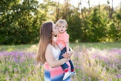 Porträt der jungen Frau ihren kleinen Kleinkindsohn auf einer sonnigen Wiese umarmend Stockfotos