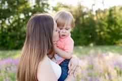 Porträt der jungen Frau ihren kleinen Kleinkindsohn auf einer sonnigen Wiese umarmend Lizenzfreie Stockfotografie
