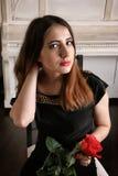 Porträt der jungen Frau im Abendkleid mit einer roten Rose in seinen Händen Lizenzfreie Stockfotos