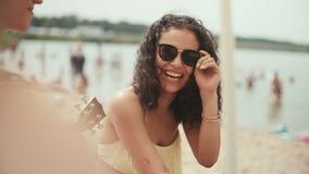 Porträt der jungen Frau im Bikini, der mit Freunden auf dem Strand und dem Lächeln sitzt stock video