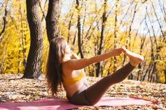 Porträt der jungen Frau im Herbststadtpark Sportmädchen, das draußen Yoga tut Lizenzfreie Stockfotografie