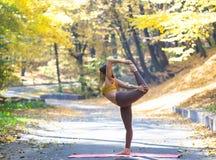 Porträt der jungen Frau im Herbststadtpark Sportmädchen, das draußen Yoga tut Stockbild