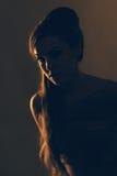 Porträt der jungen Frau im Restlicht, das unten schaut Lizenzfreie Stockfotos