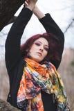 Porträt der jungen Frau im schwarzen Mantel und bunten im Schal im Freien im Park gegen Baumwintertag stockfotos