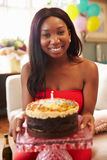 Porträt der jungen Frau Kerze auf Geburtstags-Kuchen heraus durchbrennend Stockfotos
