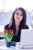 Porträt der jungen Frau mit Bündel von Tulpen und von Laptop Stockfotos