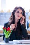 Porträt der jungen Frau mit Bündel von Tulpen, von Laptop und von Mobile Stockfoto
