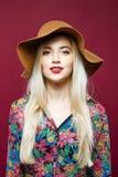 Porträt der jungen Frau mit Berufsmake-up im Hut und im bunten Hemd Erstaunliche Blondine wirft auf rosa Hintergrund auf Stockfotos