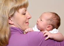 Porträt der jungen Frau mit dem Baby auf Händen Lizenzfreies Stockbild