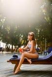 Porträt der jungen Frau mit dem Cocktailglas, das in der tropischen Sonne nahe Swimmingpool auf einem Klappstuhl mit Palme kühlt Stockfotografie