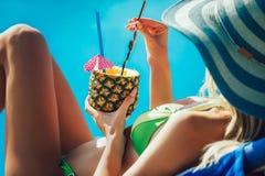 Porträt der jungen Frau mit dem Cocktailglas, das in der tropischen Sonne kühlt stockfotografie