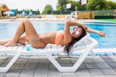 Porträt der jungen Frau mit dem Cocktailglas, das in der tropischen Sonne nahe Swimmingpool auf einem Klappstuhl kühlt Schöne jun lizenzfreie stockfotografie