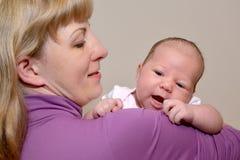 Porträt der jungen Frau mit dem netten Baby auf Händen Stockbild