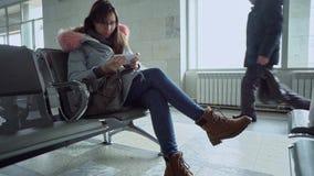Porträt der jungen Frau mit dem Smartphone, der am Bahnhof sitzt stock video